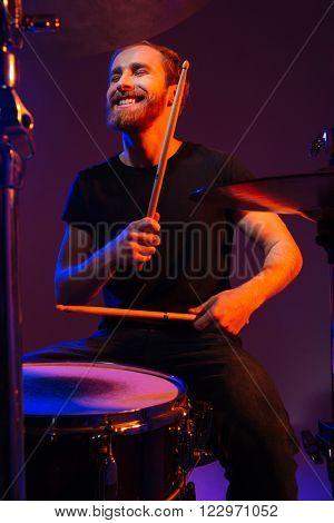 Happy cheerful bearded man drummer playing on his kit with sticks over dark background
