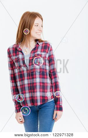 Smiling woman standing with soap bubbles and looking away isolated on a white background
