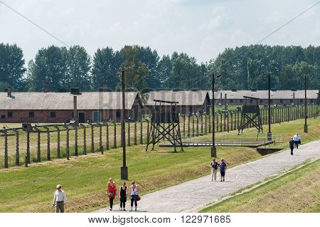 OSWIECIM, POLAND - JULY 3, 2009: Auschwitz II - Birkenau Sector I barracks and watch towers with inner perimeter electrified fence