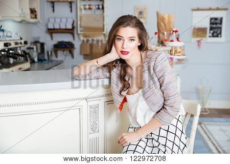 Portrait of attractive young woman with red lips sitting in cafe