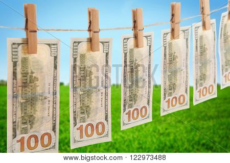 Concept of money laundering - dollars are drying on cord on field background