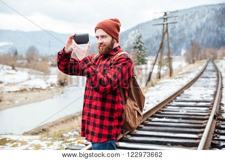 Smiling beautiful young man in checkered shirt and hat taking pictures with smartphone in mountains