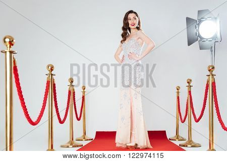 Happy woman in fashion dress posing on red carpet