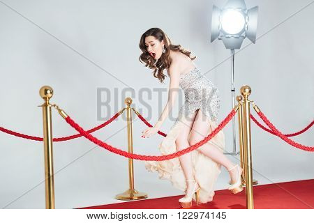 Charming woman falling on red carpet