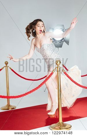 Young woman falling on red carpet