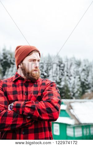 Serious bearded young man standing with hands folded  in winter village near forest