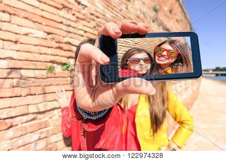 Hipster cool girls taking picture on smartphone self-portrait with screen view - Happy friends having fun together making funny faces - New technology trends concept in urban contest - Warm filter