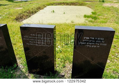 Auschwitz II - Birkenau memorial plaques in front of an ashes pit next to the Crematorium II
