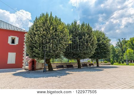 CETINJE, MONTENEGRO - AUGUST 11, 2015: Old linden trees are urban gathering place famous  by its shade on summer days, and tourists passing by on the Dvorski square.