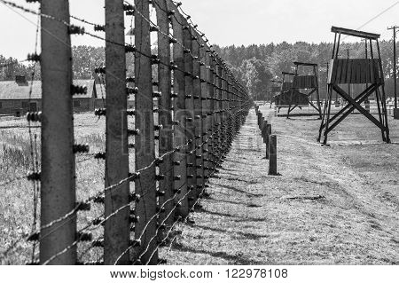 OSWIECIM, POLAND - JULY 3, 2009: Auschwitz II - Birkenau, aspect of the electrified barbed wire fence and watch towers