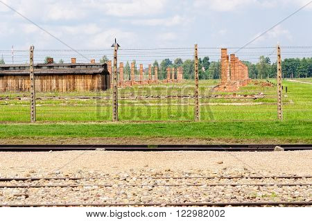 OSWIECIM, POLAND - JULY 3, 2009: Auschwitz II - Birkenau, Sector II barracks stripped after the war of their wood exteriors for rebuilding or heating purposes, exposing the brick heating ovens and chimneys.