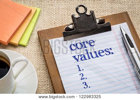 core values list on clipboard  with a pen, coffee and sticky notes against burlap canvas - business ethics and mission concept
