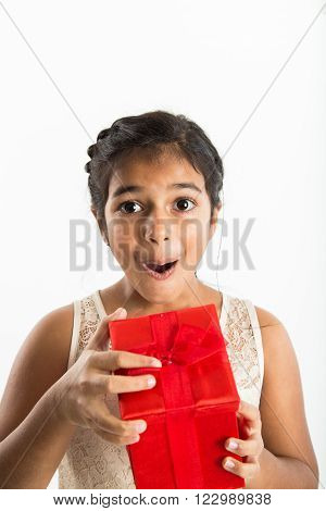 A young girl of Indian ethnicity opens a red gift box with a happy look of excitment