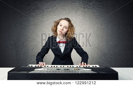 Funny crazy woman in suit and bow tie playing piano