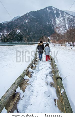 Nikko Japan - Dec 04 2015: Girls in winter clothes walking towards a mountain on a lakeside boardwalk or bridge covered with snow. Taken at Lake Yuno Yumoto Nikko Japan.