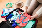 summer vacation, travel, tourism and objects concept - close up of woman packing travel bag for vaca poster