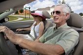 stock photo of old couple  - A happy senior couple driving a convertible car wearing sunglasses - JPG
