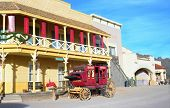 stock photo of stagecoach  - Old western style building and old stage coach - JPG