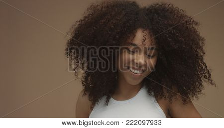 poster of mixed race black woman portrait with big afro hair, curly hair in beige background. Natural laughing