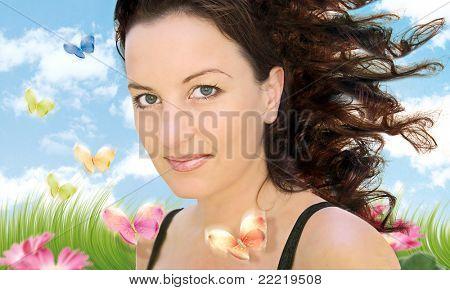 Frau in einem schönen Garten mit Blumen und Schmetterlingen