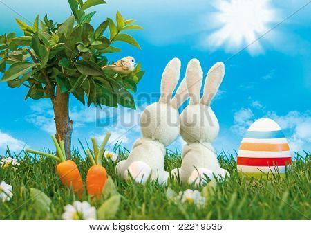 dos conejito de Pascua con huevos coloreados, sentada en un prado al lado de un árbol mirando al cielo azul