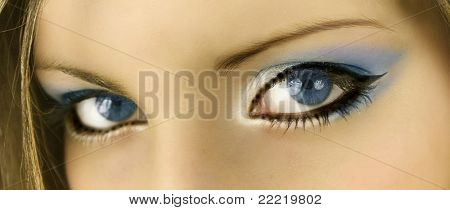 blue eyes of a woman with blue make up