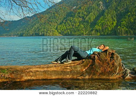 A man lies on  a trunk in the water on a lake. The unique keyword for this collection is: lake77
