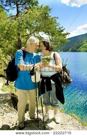 lindo casal maduro caminhadas ao lado de um lago