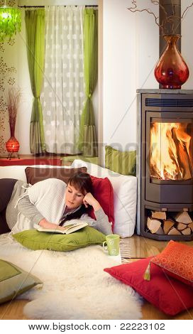 woman reading a book relaxing beside a fireplace.