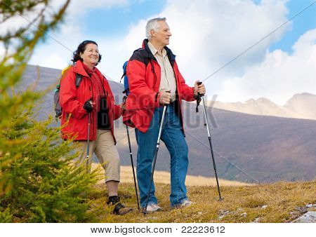 cute seniorcouple hiking in an autumn mountainlandscape