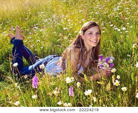 beautiful young girl lying in a marguerite meadow