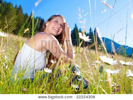 young pretty girl sitting in a marguerite-meadow
