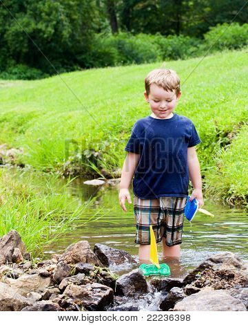 Boy has fun by playing with toy boats in creek at park during spring or summer