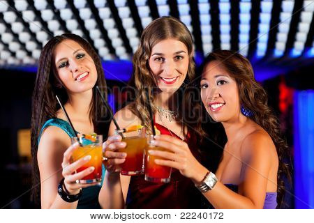 Group of party people - three friends - with cocktails in a bar or club having fun