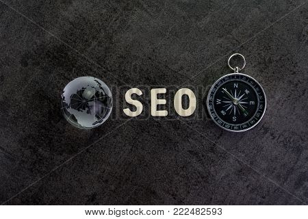 poster of Decoration globe, alphabet SEO and compass on dark cement chalkboard background using as SEO Search engine optimization concept.