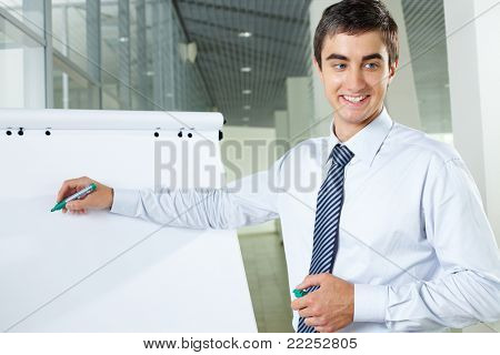Smiling businessman presenting new project to partners on a whiteboard
