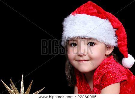 close up of süßes kleines Mädchen in Nikolausmütze Handauflegen Stock mit