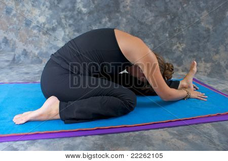 Woman On Mat In Studio Doing Yoga Pose Janu Sirsasana Or Knee To The Head