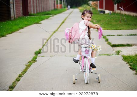 Young school girl with pink bagpack on a bicycle