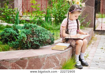 Young girl with bagpack reads waiting for school