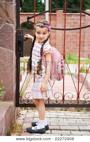 Young girl with pink bagpack leaves for school