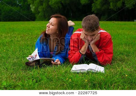 two teenagers studying outdoors on grass