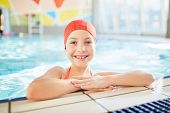 Happy little girl in swimwear looking at camera out of swimming-pool poster