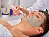 Mud facial mask of man in spa salon. Massage with clay full face in therapy room. Man lying on spa b poster