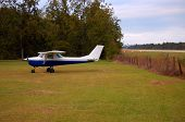 stock photo of cessna  - 1966 Cessna tied down next to the runway - JPG