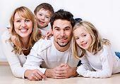 image of family fun  - sweet young family having fun on the floor in their home - JPG
