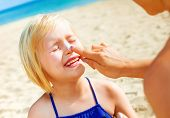 Sun Kissed Beauty. Smiling Healthy Mother And Daughter In Beachwear On The Seacoast Applying Sun Cre poster