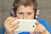 Boy With Headphones And Mobile Phone In Hand poster