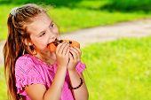stock photo of hot dogs  - A girl is eating her hot dog outdoors - JPG