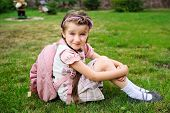 foto of bagpack  - Young school girl with pink bagpack sits on grass - JPG